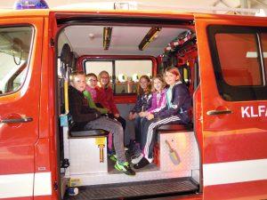 Gemeinsam.Sicher.Feuerwehr - Kinder der dritten und vierten Klasse Volksschule sitzen im KLF
