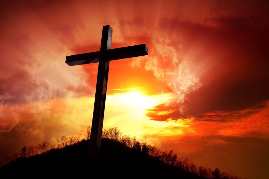 Kreuz auf einem Hügel vor dem Sonnenuntergang